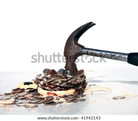 a hammer breaks a piggy bank with money and parts flying all over - stock photo