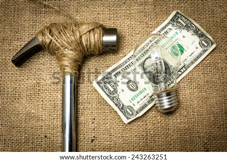 A hammer stopped from destroying the dollar with a lightbulb