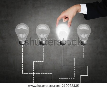 A hand chooses one lightbulb out of four other. A metaphor of the right decision. - stock photo