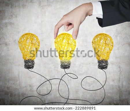 A hand chooses one lightbulb out of three other. A metaphor of the right decision.  - stock photo