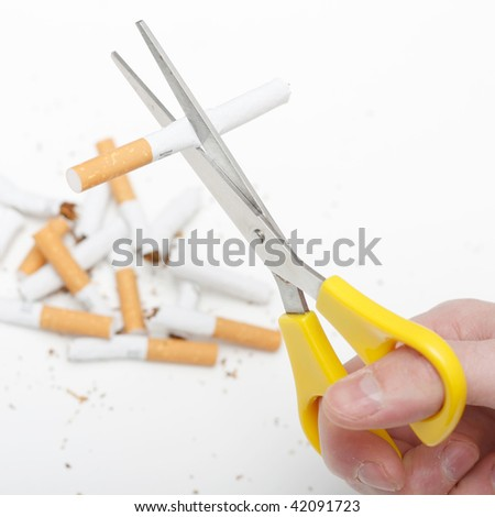A hand cutting cigarettes - stock photo