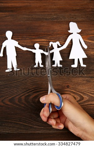 A hand cutting paper chain of a family, divorce and child custody battle - stock photo