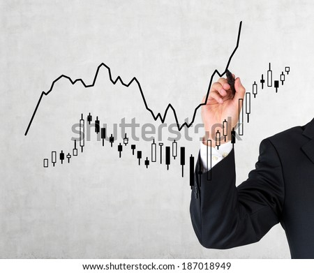 A hand drawing a market bar-chart  - stock photo