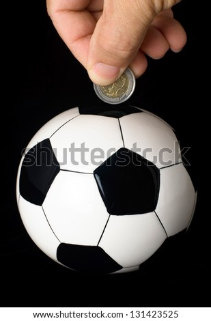 A hand drops a coin into a piggy bank in the shape of a soccer ball. - stock photo