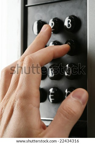 a hand entering a code into the keypad - stock photo