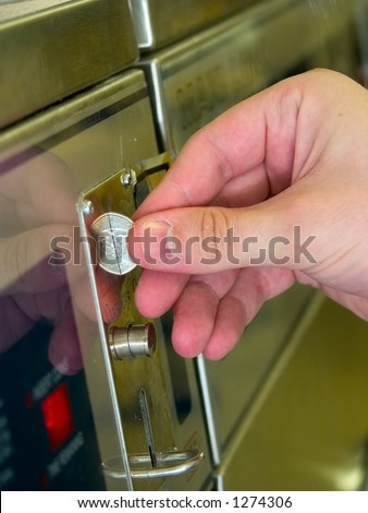 A hand feeding U.S. quarters into a washing machine at a laundromat. - stock photo