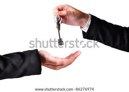 A hand giving a key to another hand. Both persons in suits. Isolated. - stock photo