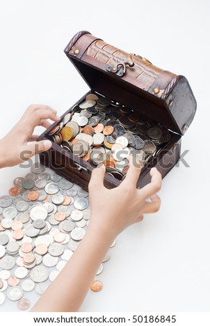 A hand grab the wooden treasure box loaded with coins - stock photo