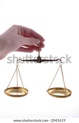 A hand holding a balance scale. - stock photo