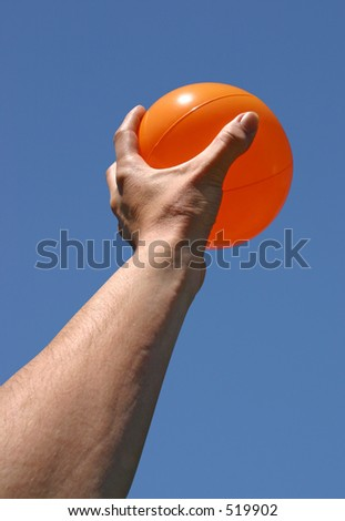 A hand holding a bright orange ball against a clear blue sky. Clipping path included.