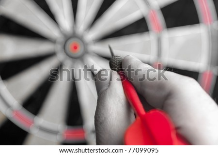A hand holding a dart getting ready to aim at the dartboard. Shallow depth of field. - stock photo