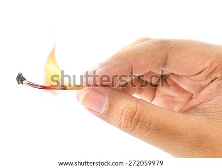 A hand holding a fired matchstick on a white background - stock photo