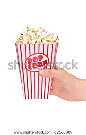 A hand holding a full popcorn box isolated against white background