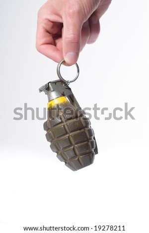 A hand holding a green combat pineapple grenade hanging by the trigger. - stock photo