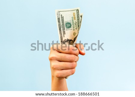 A hand holding a handful of twenty us dollars, on blue background. - stock photo