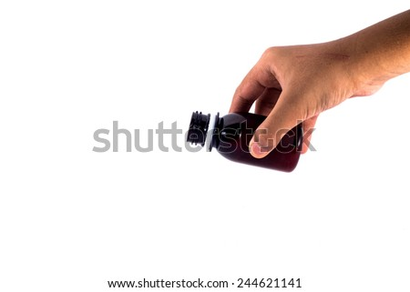 A hand holding a medicine bottle in action to pour the syrup into something isolated on white background - stock photo