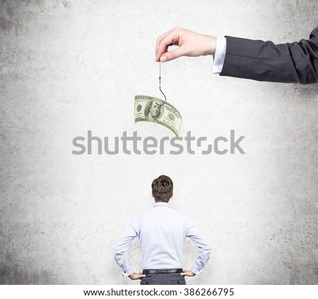 A hand holding a one-hundred dollar banknote on a thread, a businessman with hands on hips looking at it. Back view. Concrete background. Concept of motivation. - stock photo