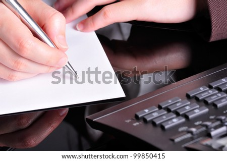 A hand, holding a pen, is ready to write on a document with a telephone next to it. - stock photo