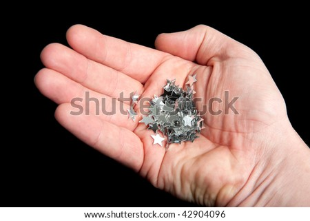 A hand holding a pile of stars isolated on a black background.