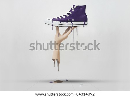 A hand holding a purple sneaker, melted all over the floor. - stock photo