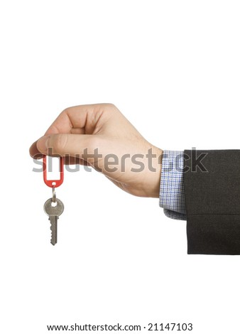 A hand holding a red keyring with a blank label and a key. - stock photo