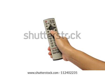 A hand holding a remote control - stock photo