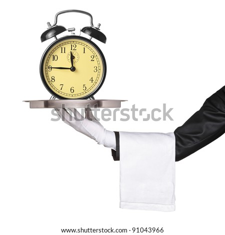A hand holding a silver tray with a retro clock alarm on it isolated on white background