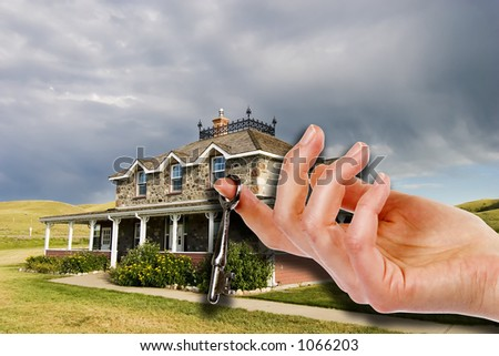 A hand holding a skeleton key in front of an old masion. - stock photo