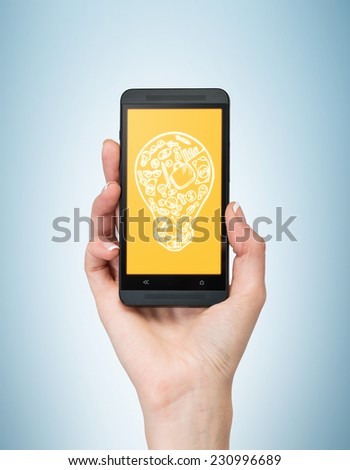 A hand holding a smartphone with the sketch of the light bulb.  - stock photo