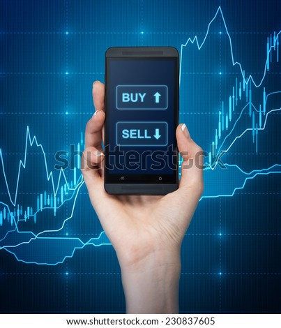 A hand holding a smartphone with words 'sell' and 'buy' over the forex background. - stock photo