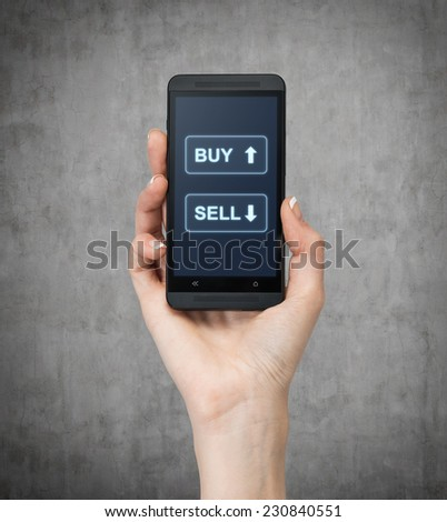 A hand holding a smartphone words sell'' and 'buy' over the concrete background. - stock photo
