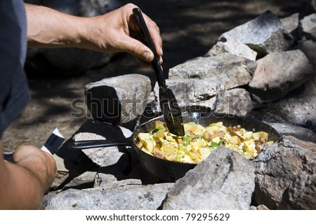 A hand holding a spatula, cooking breakfast over a campfire. - stock photo