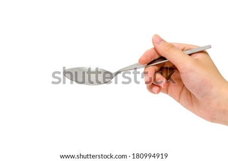 a hand holding a stainless-steel spoon - stock photo