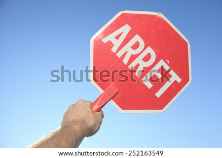 A hand holding a stop sign blue sky background. - stock photo