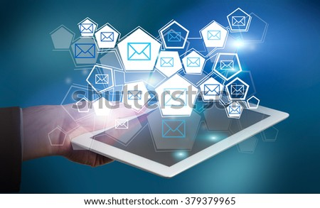 A hand holding a tablet, many halogen envelopes in hexahedrons over it. Dark blurred background. Concept of Internet communication.
