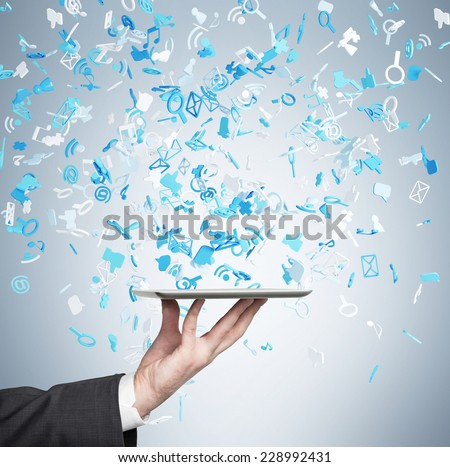 A hand holding a tablet with flying social networking icons. Blue background.  - stock photo