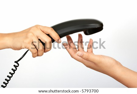 A hand holding a  telephone handset over a white background