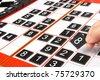 A hand holding a tiles  on a sudoku grid - stock photo