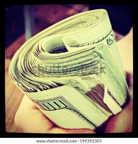 A hand holding a wad of cash with Instagram filter. - stock photo