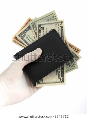 A hand holding a wallet with some dollar bills - stock photo