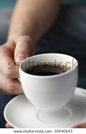 A Hand holding a white cup of black coffee