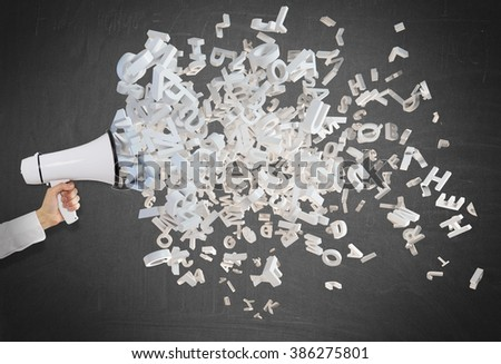 A hand holding a white loudspeaker, letters flying out from it. Side view. Black background. Concept of informing - stock photo