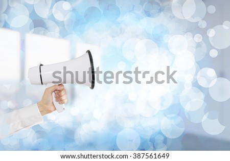 A hand holding a white loudspeaker. Side view. Bubbles and blurred office at the background. Concept of informing - stock photo