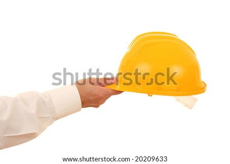 A hand holding a yellow security helmet isolated on white - stock photo