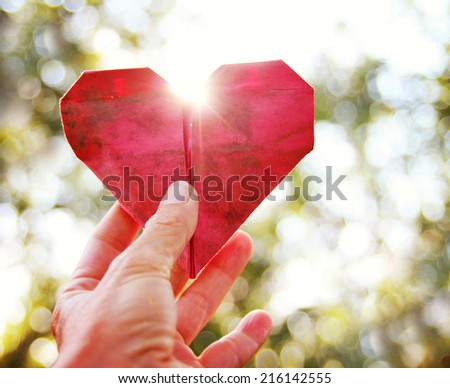 a hand holding an origami paper heart up to the sun during sunset - stock photo