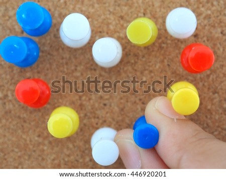 A hand holding blue pushpin with cork board background, colorful many pin - stock photo