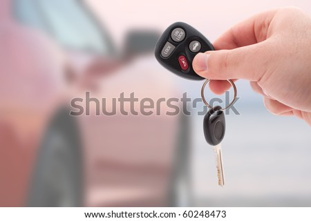 A hand holding car keys and a remote control for keyless entry. - stock photo