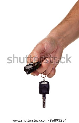 A hand holding car keys and a remote control for keyless entry. Isolated over white