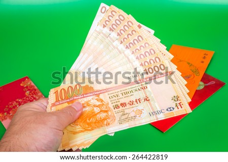 a hand holding money, Singapore dollars note in a red envelope - stock photo