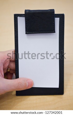 A hand holding restaurant bill to check the order before pay - stock photo